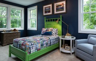 Boy's bedroom with navy walls and bright green bed
