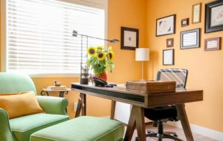 Home office painted orange with green chair