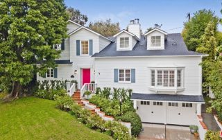 Large, traditional gray home with a bright red door